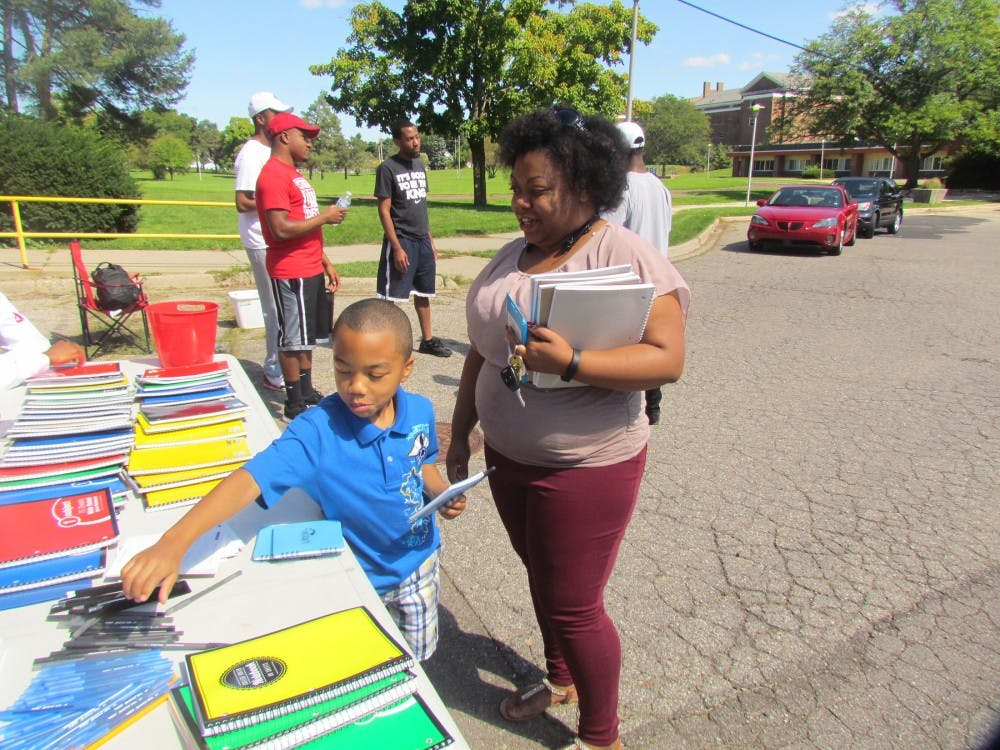 Michelle Coleman, right, and her son Malik Nichols, 7, look at school supplies on Sept. 3, 2016 at 730 W Maple St. in Lansing.