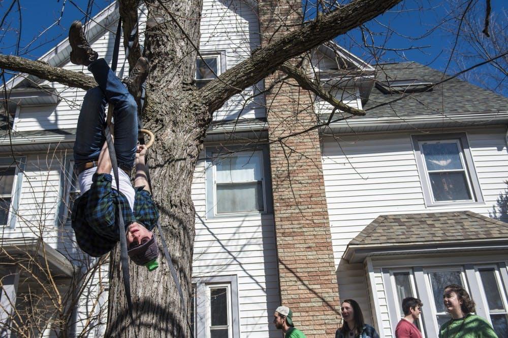 <p>Astrophysics junior Austin Czyzewski hangs upside down during St. Patrick's Day on March 17, 2018 at Orion House along M.A.C. Avenue.</p>