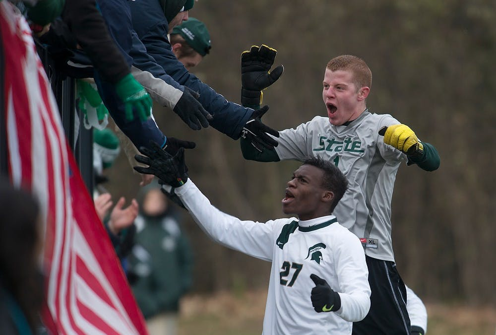 """<p>Junior midfielder Fatai Alashe, 27, and sophomore goalkeeper Zach Bennett celebrate with the Red Cedar Rowdies on Nov. 24, 2013, after defeating Louisville during the second round of the <span class=""""caps"""">NCAA</span> tournament at DeMartin Stadium at Old College Field. The Spartans defeated the Cardinals 1-0 in double overtime. Julia Nagy/The State News</p>"""