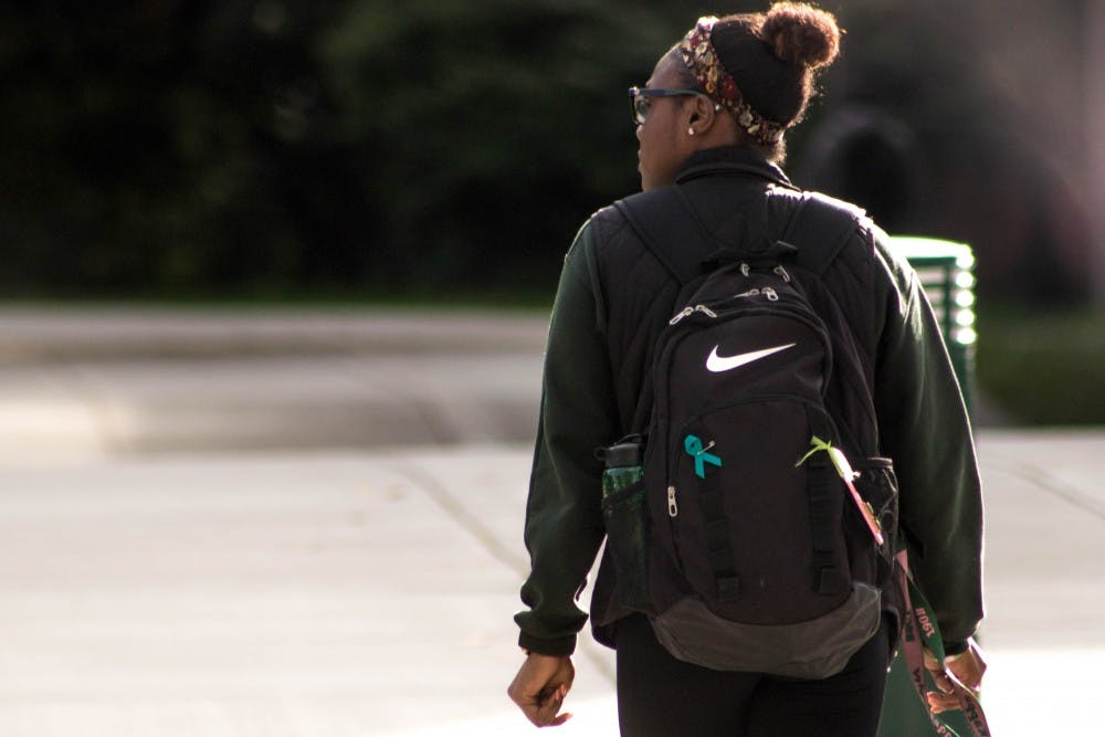 A student crosses Harrison in front of Brody Hall on Sept. 26, 2018. The teal ribbon symbolizes support for sexual assault survivors.