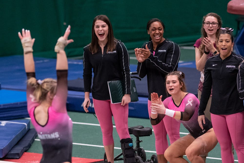 <p>The Spartans cheer for Chloe Bellmore during the meet against Minnesota Jan. 18, 2020 at Jenison Fieldhouse. The Spartans defeated the Buckeyes, 195.450-195.325.</p>