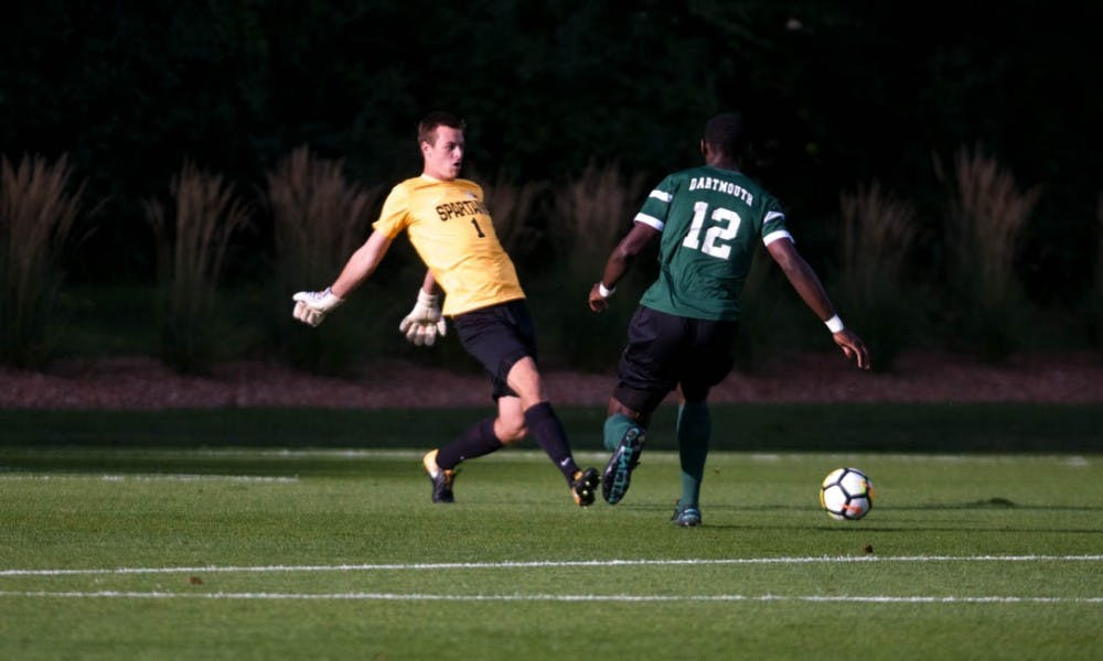 <p>Senior goalkeeper Jimmy Hague (1) beats out Dartmouth forward Eduvie Iboka (12) during a game against Dartmouth on Sep. 1, 2017 at DeMartin Stadium at Old College Field. The Spartans defeated the Big Greens 1-0.</p>
