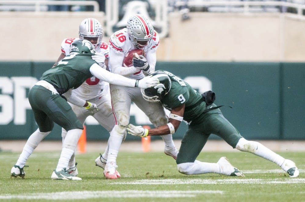 Junior safety Montae Nicholson (9) and senior cornerback Darian Hicks (2) tackle Ohio State quarterback J.T. Barrett (16) during the game against Ohio State on Nov. 19, 2016 at Spartan Stadium. The Spartans were defeated by the Buckeyes, 17-16.