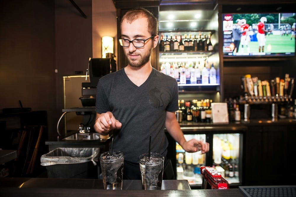 <p>Alumnus and East Lansing resident Seth Zundel prepares drinks, July 30, 2014, at Black Cat Bistro in East Lansing. Zundel graduated with a degree in English in May, 2013 and is currently a server at Black Cat Bistro. Corey Damocles/The State News </p>
