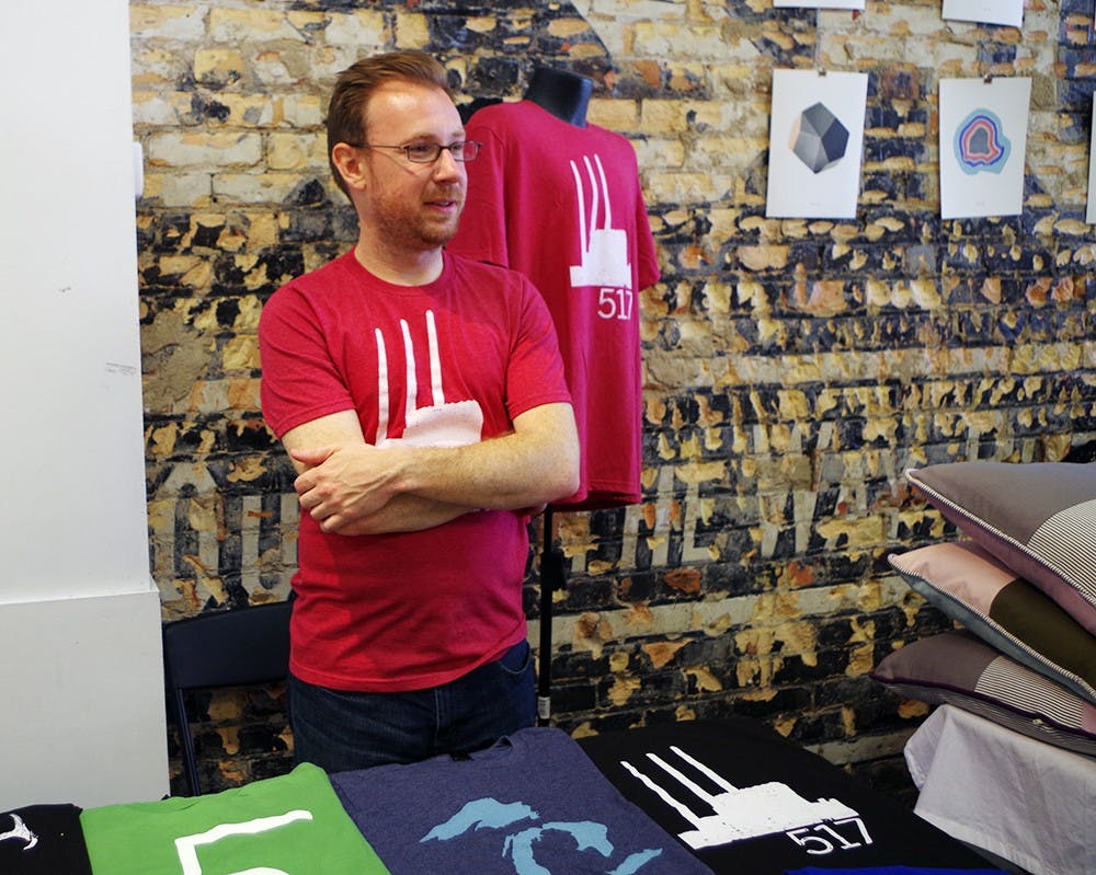 <p>Ty Forquer, the owner of 517 Shirts, talks with a customer at River City MRKT June 6, 2015, in REO Town, Lansing. 517 shirts represent Lansing and Michigan in their designs. Yuanzhe Zhuang/The State News</p>