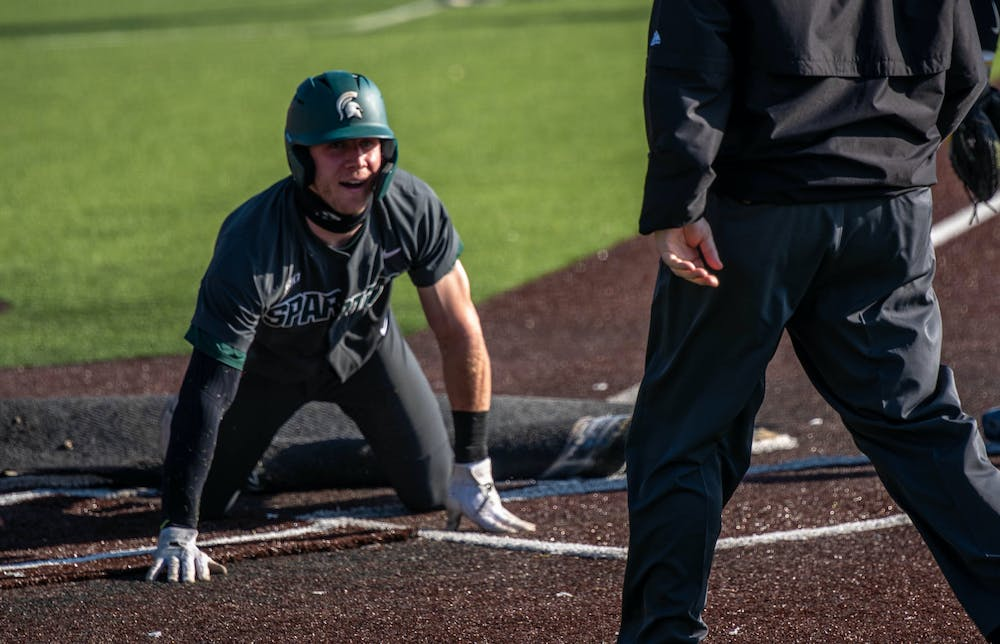 <p>Senior outfielder Joe Stewart (5) slides into home during the fourth inning. The Wolverines made a comeback in the ninth inning to top the Spartans, 8-7, at Ray Fisher Stadium on March 21, 2021.</p>