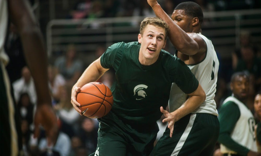 Junior forward Colby Wollenman looks up to attempt a point Oct. 24, 2014, during Midnight Madness at Breslin Center. Head Coach Suzy Merchant performed as Beyonce and Head Coach Tom Izzo performed as a member of KISS. Erin Hampton/The State News