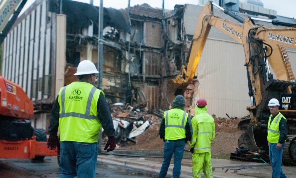 <p>Construction workers supervise the ongoing &nbsp;demolition of the blighted building on Oct. 7, 2017, at the corner of Grand River and Abbot. The building began to be torn down at 7:30 in the morning.</p>