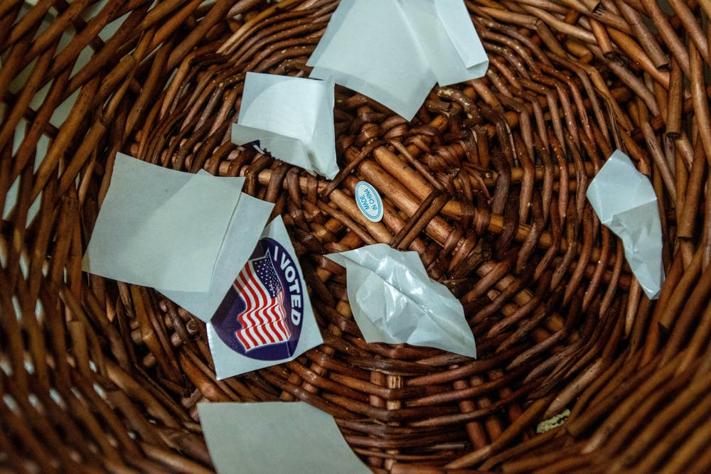 """Wrappings of """"I voted stickers"""" sit in a bin at Willow Elementary in Lansing on Nov. 3, 2020. This site houses two precincts and had people trickling in for both precincts."""