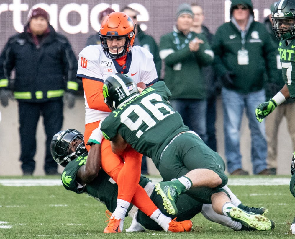 Junior linebacker Antjuan Simmons (34) and junior defensive end Jacub Panasuik (96) tackle the Illinois quarterback during the game against Illinois Nov. 9, 2019 at Spartan Stadium.