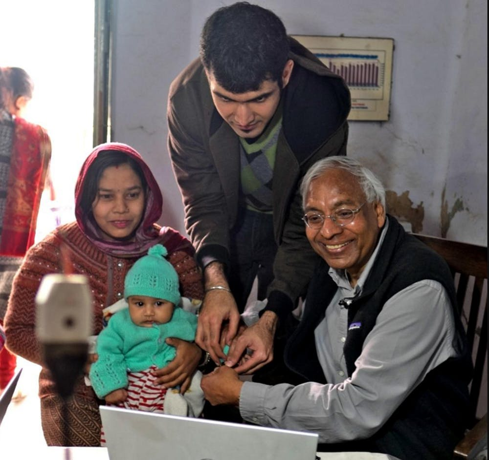 <p>MSU Biometrics Research Group leader and&nbsp;computer science professor Anil Jain, right, and doctoral&nbsp;student and biometrics group&nbsp;researcher Sunpreet Arora, next over,&nbsp;collect fingerprint data during&nbsp;the group's January&nbsp;research trip to India. Courtesy of MSU Biometrics Research Group.</p>