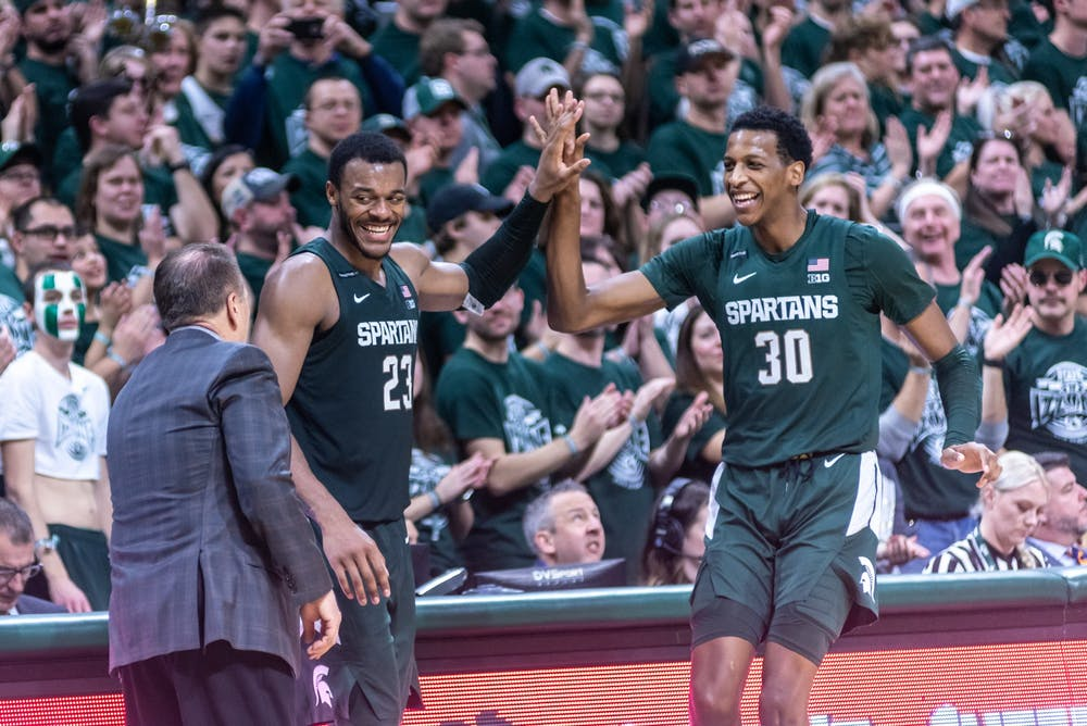 <p>Junior forward Xavier Tillman (23) and sophomore forward Marcus Bingham Jr. (30) high five each other after being subbed out against Illinois. The Spartans defeated the Illini, 76-56, on Jan. 2, 2020 at the Breslin Student Events Center.</p>