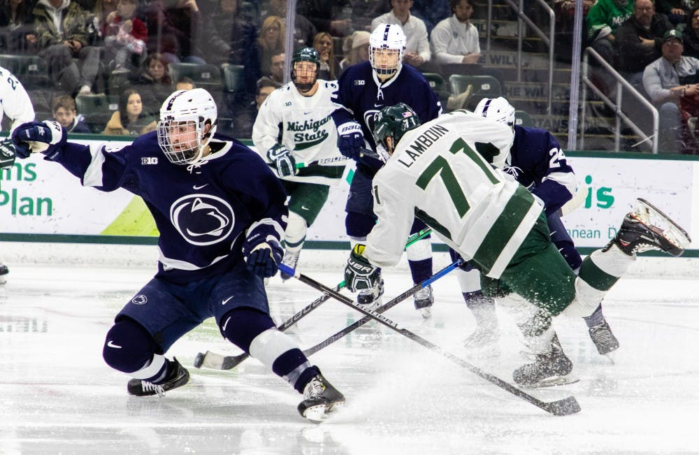 Junior wing Logan Lambdin (71) splits defenders during the game against Penn State on Feb.16, 2019. The Spartans fell to the Nittany Lions 5-3.