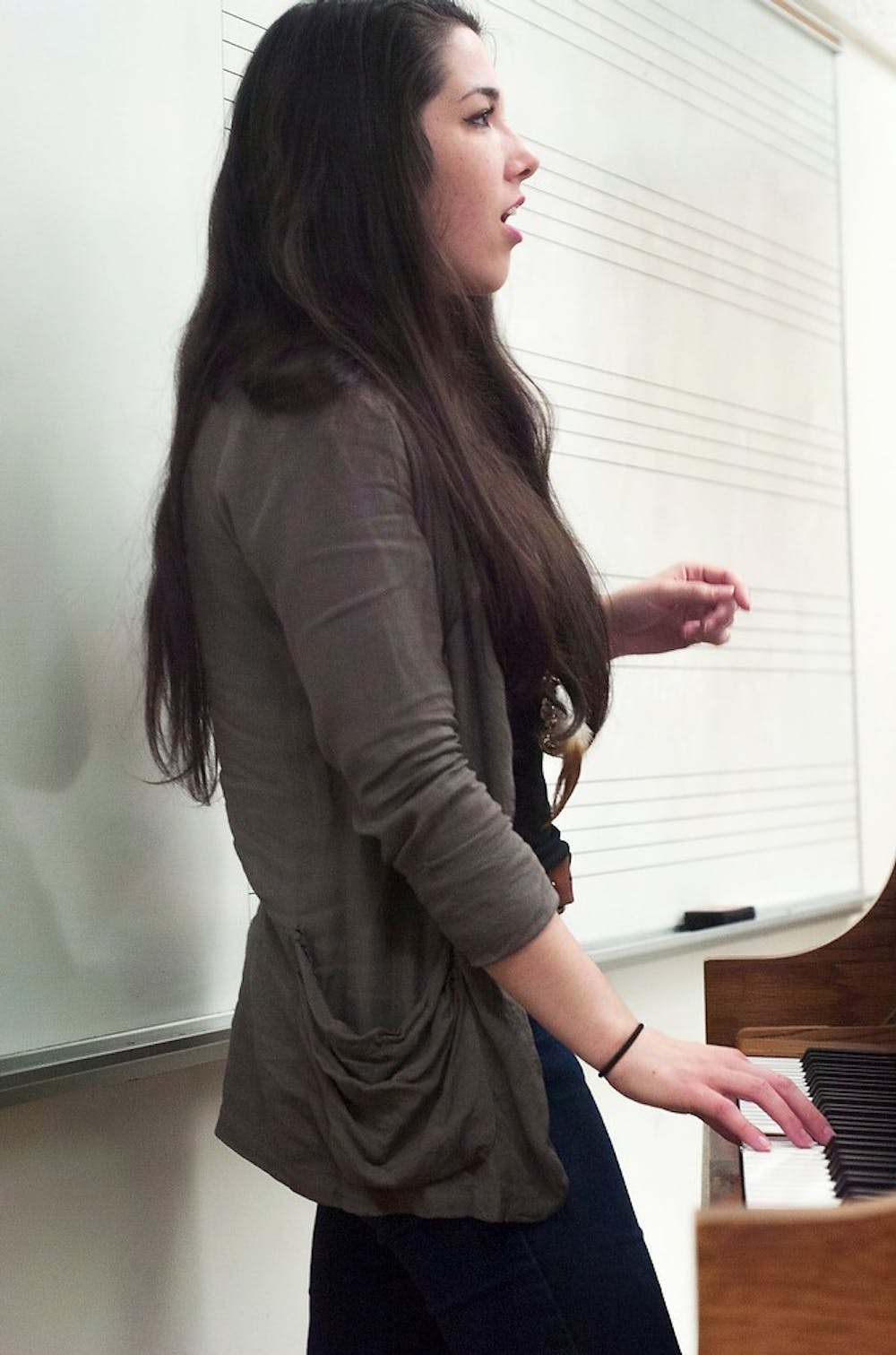 <p>Hospitality business sophomore and Capital Green A Capella member Hannah Schroeder assists students auditioning for the group by playing scales April 15, 2014, at Music Practice Building. Schroeder played notes while students repeated the notes to demonstrate their vocal range. Meagan Beck/The State News</p>