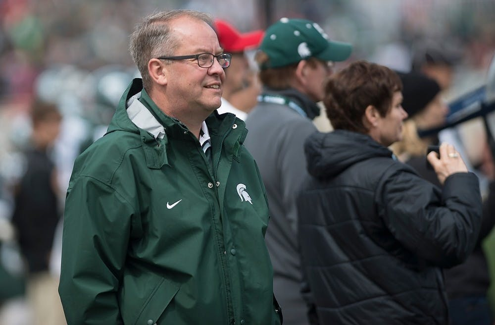 Athletic director Mark Hollis watches the team on the field April 25, 2015, during the Green and White Spring Game at Spartan Stadium. The White team defeated the Green team, 9-3.
