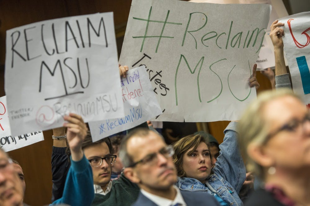 Protesters from Reclaim MSU hold signs during the Board of Trustees meeting on Feb. 16, 2018 at the Hannah Administration Building. (Nic Antaya | The State News)