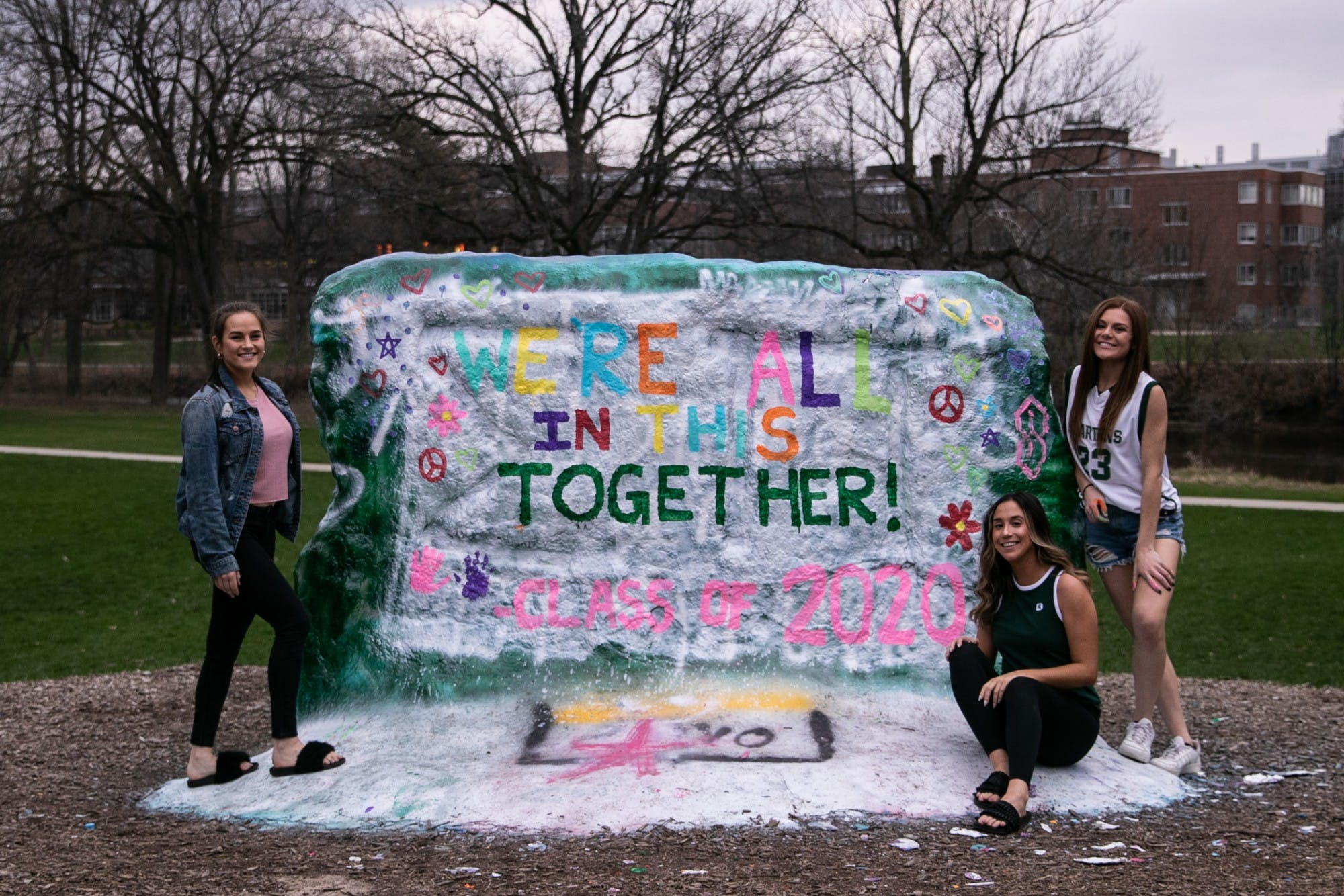 Three young people pose in front of a large painted rock. On the rock are the words 'We're all in this together! Class of 2020'