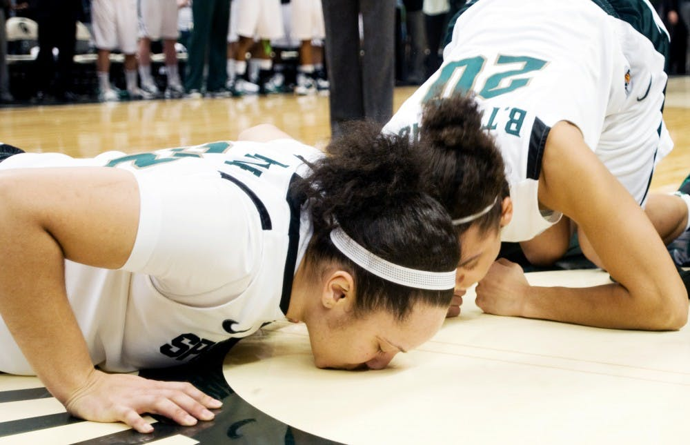 Seniors Kalisha Keane and Brittney Thomas kiss the floor after their final home game on Thursday  against Ohio State at Breslin Center. It is tradition the seniors of the men's and women's basketball teams kiss the floor as a final goodbye. Lauren Wood/The State News