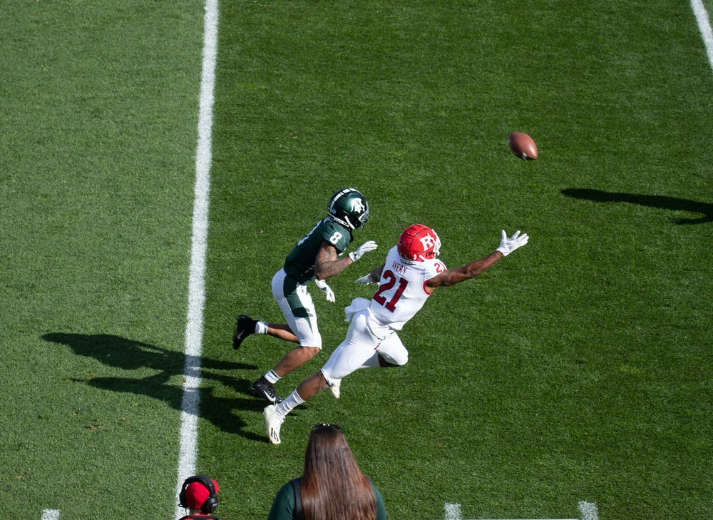<p>Wide receiver Jalen Nailor, 8, attempts to receive a pass in a game against Rutgers on Oct. 24, 2020. Defensive back Tre Avery, 21, nearly intercepts the pass.</p>