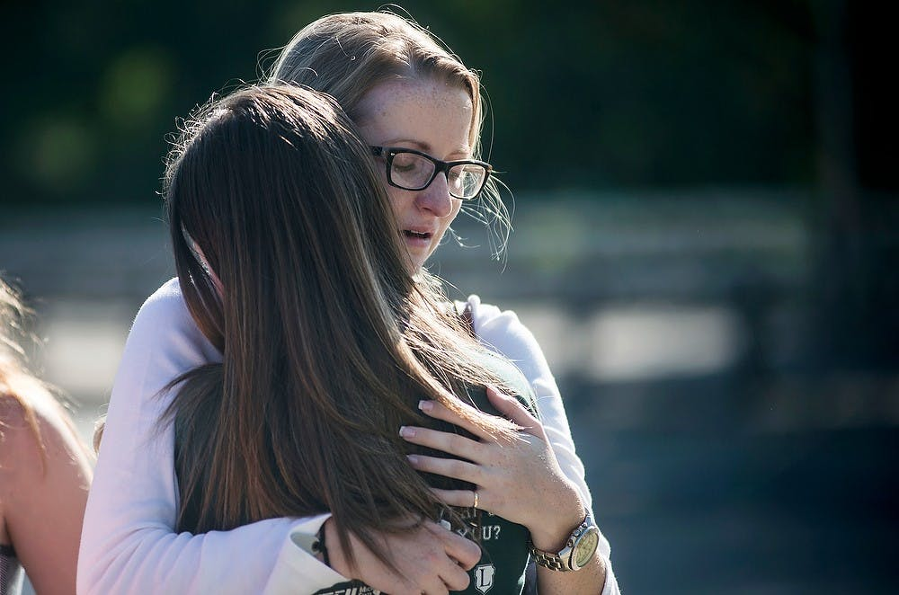 <p>Dietetics senior Hannah Byrne, right, hugs hospitality business junior Ashley Day on Sept. 28, 2014, during accounting senior Morgan McGregor's memorial at the Rock on Farm Lane. McGregor was pacemaker dependent. Erin Hampton/The State News</p>