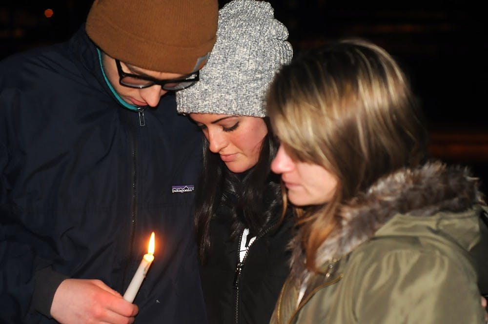 <p>Political theory junior and Sigma Pi brother Andrew Brewster, and neuroscience freshman Sabrina Saracino, middle, comfort mechanical engineering sophomore Celeste Stawiarska, right, Jan 30, 2015, during the candlelight vigil held at the The Rock on Farm Lane in honor of Stawiarska's boyfriend and applied engineering sciences senior Anthony Hawley. Kennedy Thatch/The State News</p>