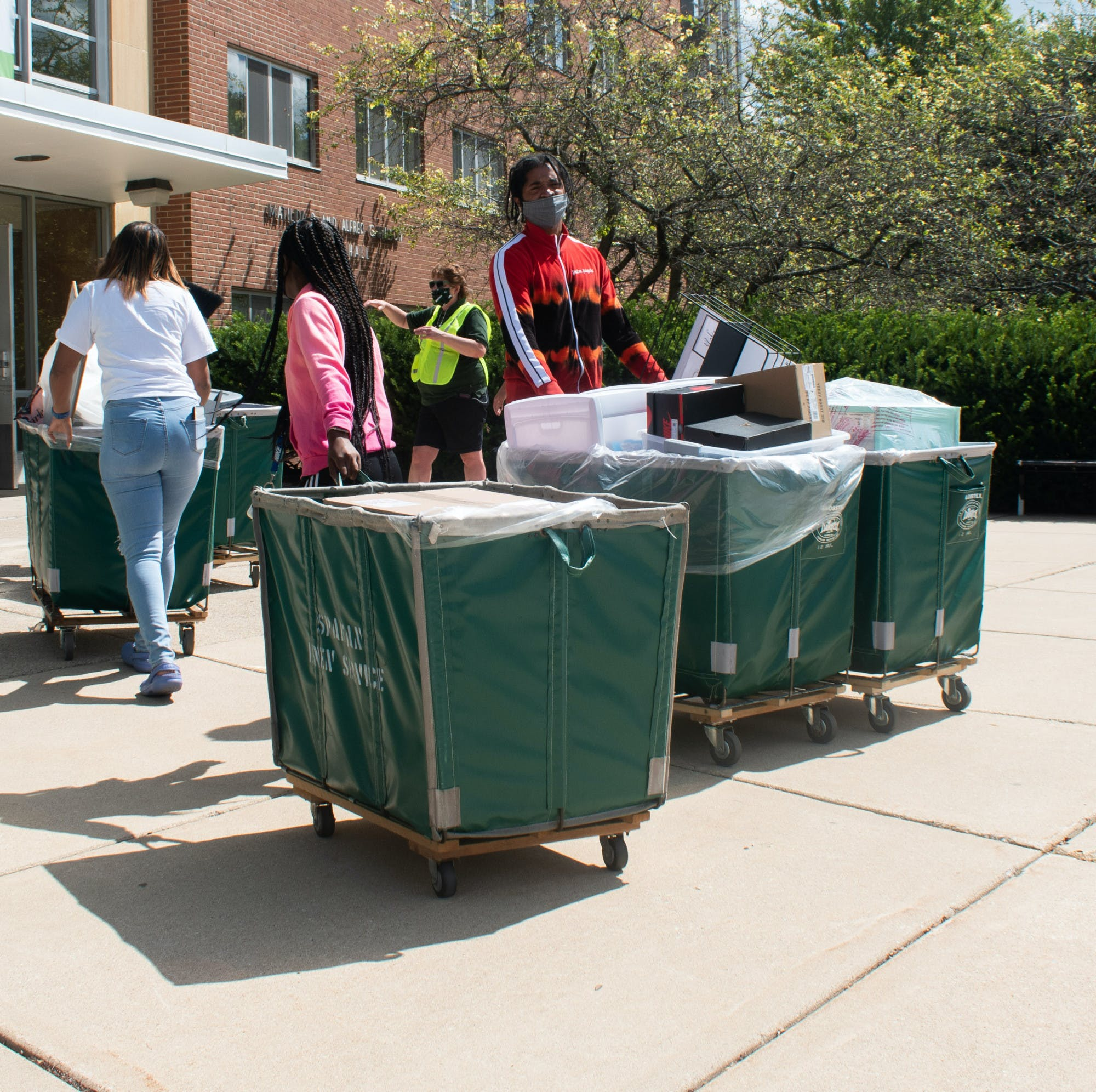 A group of people wearing face masks push and pull large moving bins into a residence hall
