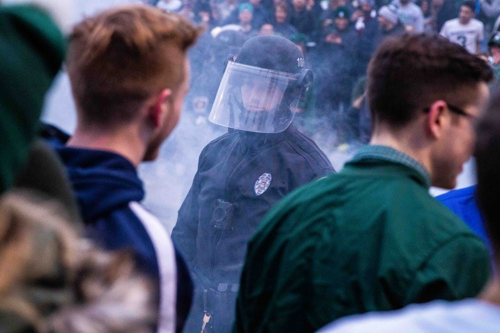 A police officer stands in the smoke of the extinguished couch after MSU's victory over Duke in the Elite Eight in Cedar Village Apartments March 31, 2019.