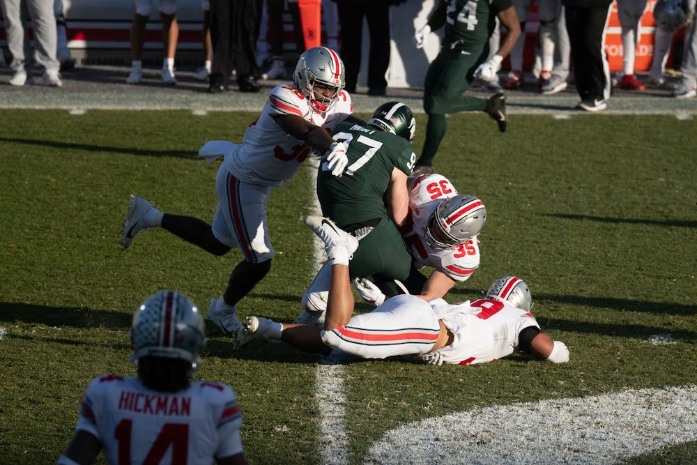 <p>MSU wide receiver Tyler Hunt (97) gets tackled by Ohio State defenders in Spartan Stadium on Dec. 5, 2020.</p>