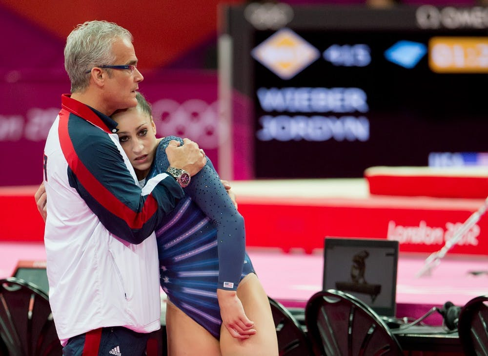 Jordyn Wieber of the United States received a hug from her coach, John Geddert, left, in the women's floor exercises apparatus finals at North Greenwich Arena during the 2012 Summer Olympic Games in London, England, Tuesday, August 7, 2012. Wieber finished seventh in the competition. Photo courtesy David Eulitt/Kansas City Star/MCT