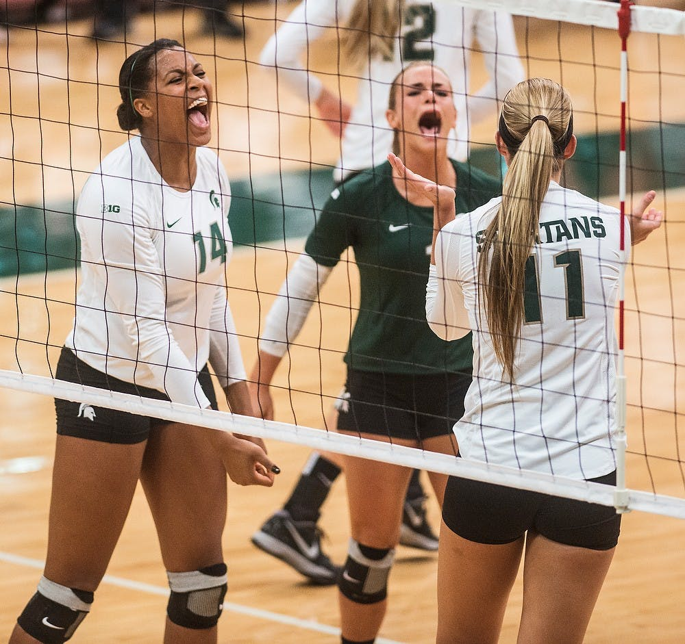 <p>Senior libero Kori Moster cheers with teammates and senior middle blocker Jazmine White and sophomore outside hitter Chloe Reinig after a point Oct. 3, 2014, during a game against the University of Michigan at Jenison Fieldhouse. The Spartans defeated the Wolverines, 3-1. Erin Hampton/The State News</p>