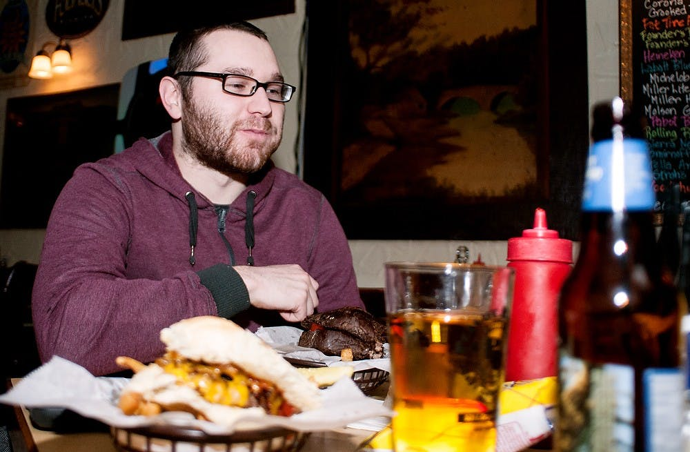 <p>Williamston, Mich., resident Christopher Cullen enjoys beer and a burger Monday at the Peanut Barrel Restaurant, 521 E. Grand River Ave. The East Lansing City Council discussed liquor license renewals at the work session Wednesday, Feb. 26, 2013, at City Hall, 410 Abbot Road. </p>