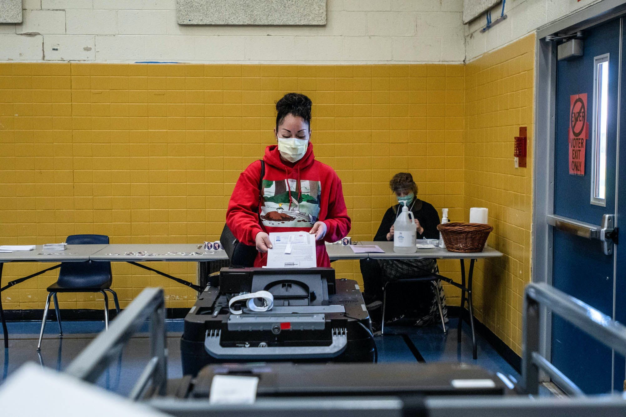AA voter feeds their ballot into a machine.