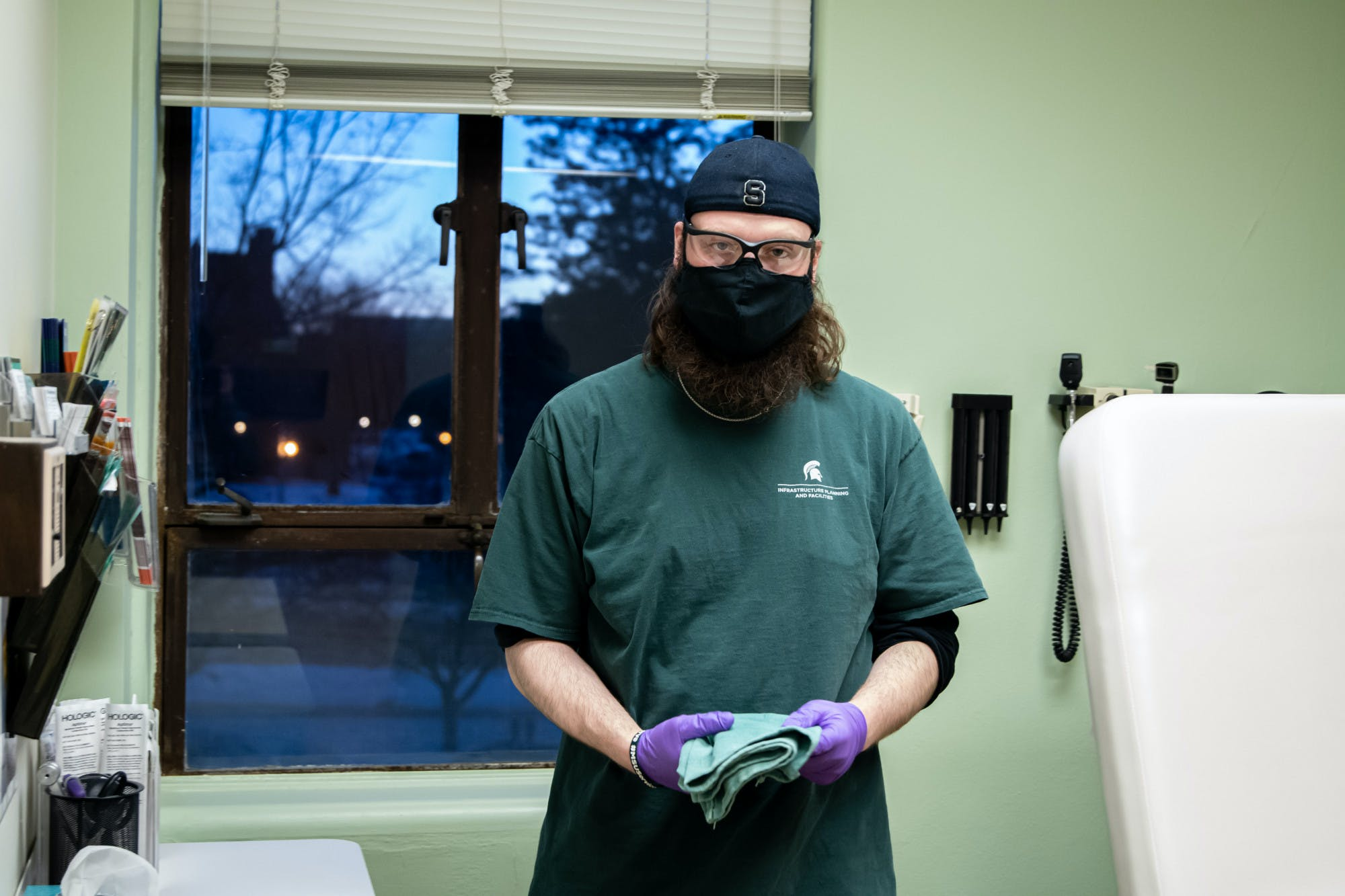 A bearded person wearing a black face mask, a backwards black Spartan cap, a green Michigan State Infrastructure Planning and Facilities t-shirt, and purple exam gloves holds a folded cloth in a medical appointment room.