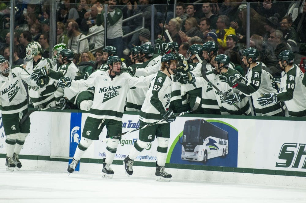The Spartans high five after scoring a goal during the second period of the men's hockey game against Wisconsin on Feb. 4, 2017 at Munn Ice Arena. The Spartans were defeated by the Badgers, 3-4.