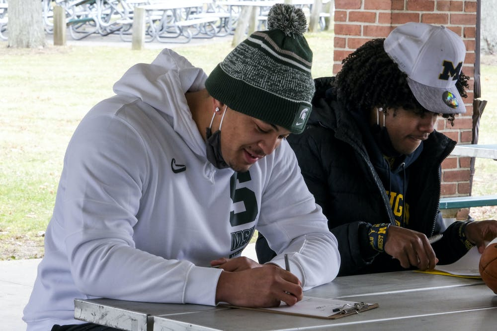 <p>MSU commit Ethan Boyd and U of M commit Andrel Anthony Jr. sign for their respective teams at Patriarche Park on Dec. 16, 2020.</p>
