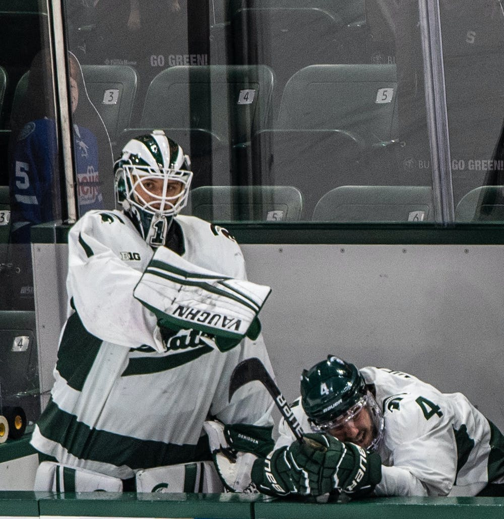 <p>DeRidder points at freshman defender Nash Nienhuis (4), who seconds before had slammed his head into the wall and skated off in pain. The Badgers shut out the Spartans 4-0 at Munn Ice Arena on March 5, 2021. </p>