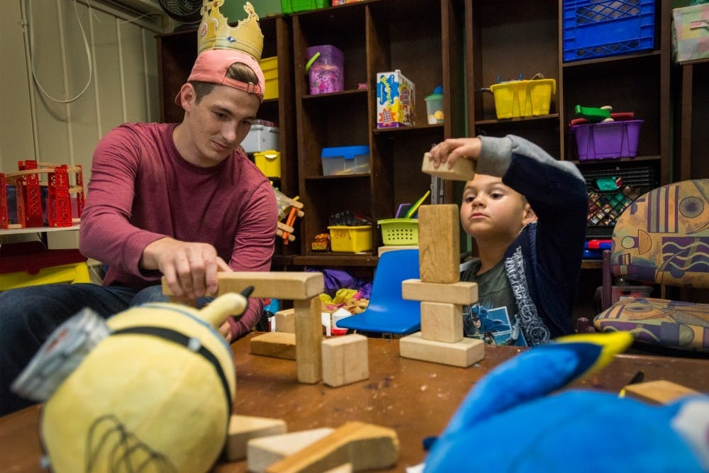 Mechanical engineering junior Josh Wojtowiczon and East Lansing resident Leon Strong, 5, play with blocks on Sept. 30, 2016 at Haven House at 121 Whitehills Drive in East Lansing. Haven House provides temporary housing for families until they are able to find permanent housing elsewhere.
