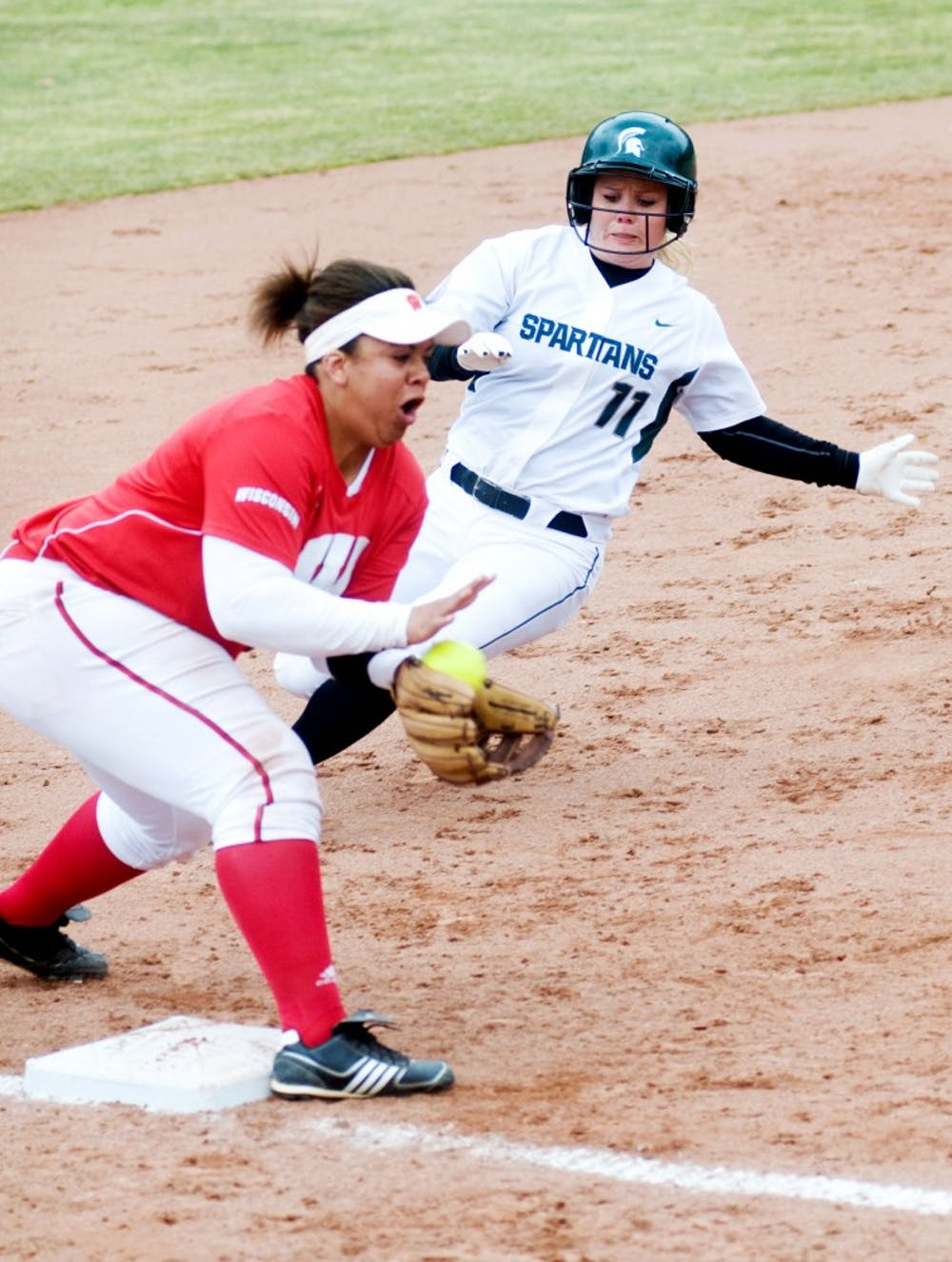 Senior first baseman Heidi Purtzer runs into third base as Wisconsin third baseman Shannel Blackshear catches the ball during Saturday's home game at Secchia Stadium. Lauren Wood/The State News
