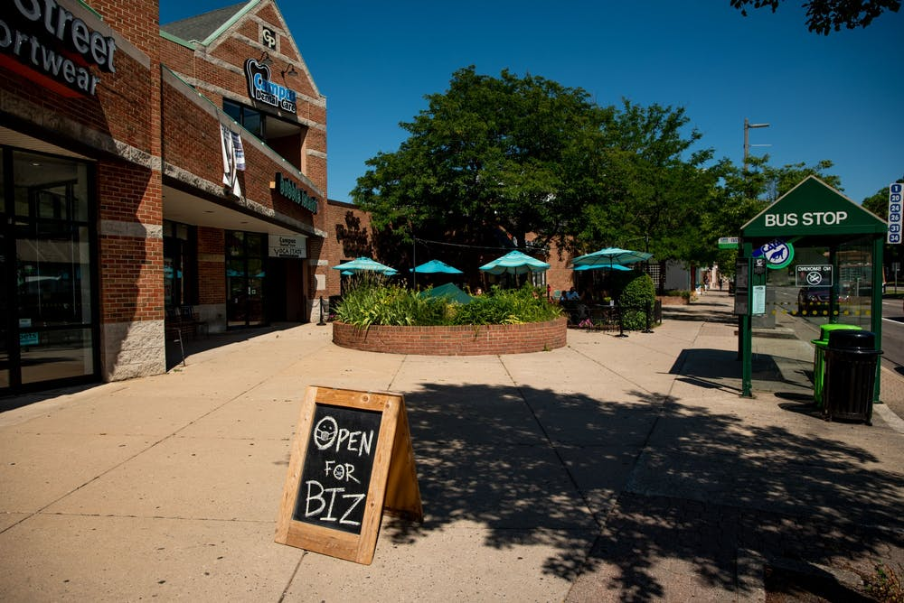 <p>A sign showing that businesses are open despite recent COVID-19 outbreaks in downtown East Lansing is pictured Jun. 30, 2020.</p>