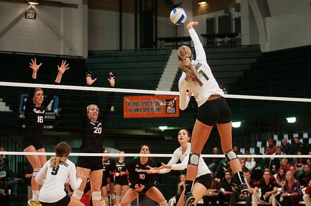 <p>Sophomore outside hitter Chloe Reinig spikes the ball as Nebraska setter Mary Pollmiller and middle blocker Meghan Haggerty attempt to block Oct. 10, 2014, at Jenison Field House. The Cornhuskers defeated the Spartans, 3-1. Aerika Williams/The State News</p>