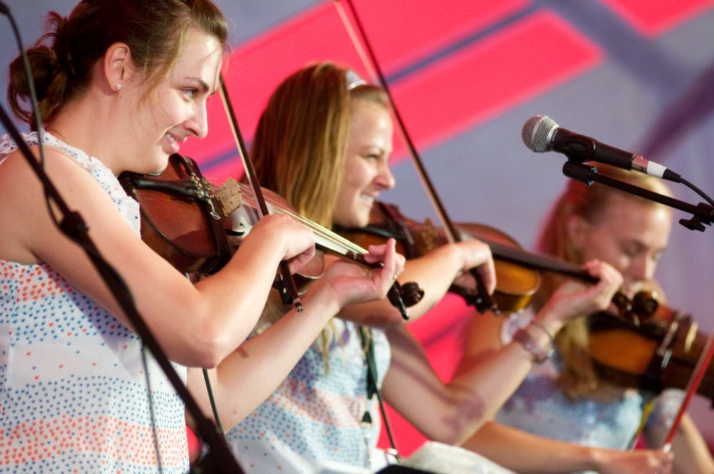 <p>From left, sisters Kristine Babiarz, Erika Piotrowski and Andrea Piotrowski, all Muskegon, Mich., residents, perform with their family band, Pan Franek and Zosia&#8217;s Polka Towners, on Sunday at the Great Lakes Folk Festival in East Lansing. </p>