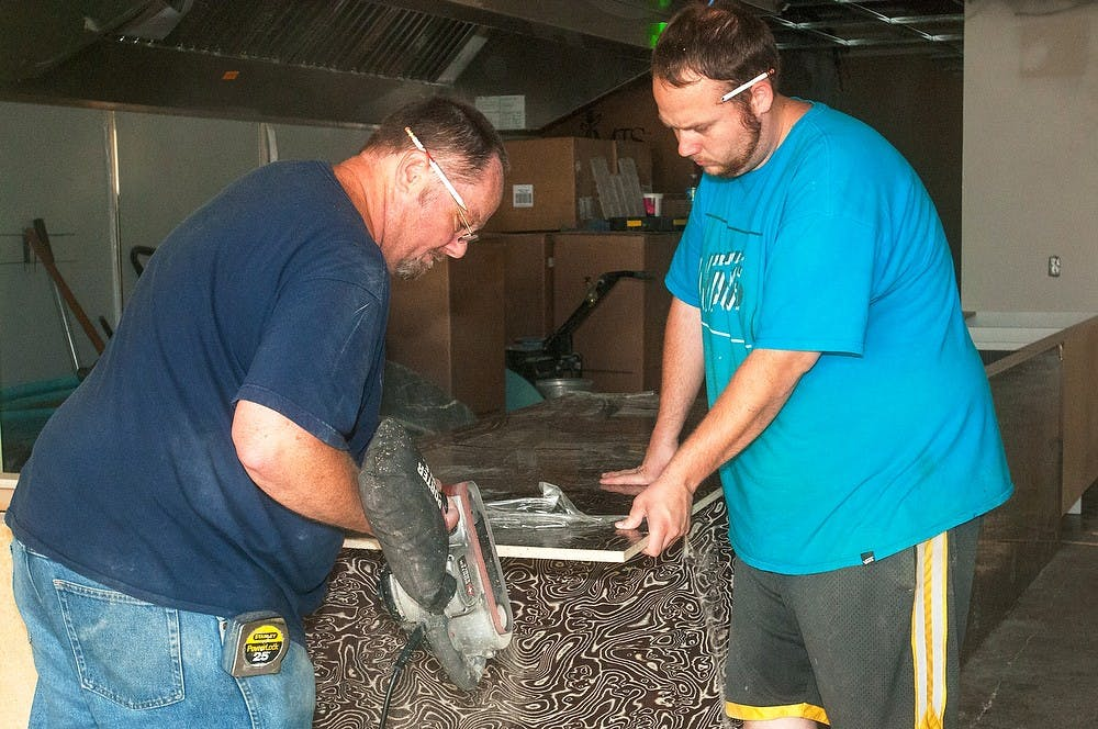 <p>From left, Milford, Mich., residents, Ed Starkey and Eddie Starkey work on construction at Sweet Lorraine's Fabulous Mac n' Cheez on July 30, 2014 on Grand River Avenue. The restaurant is scheduled to open sometime this August. Jessalyn Tamez/The State News</p>