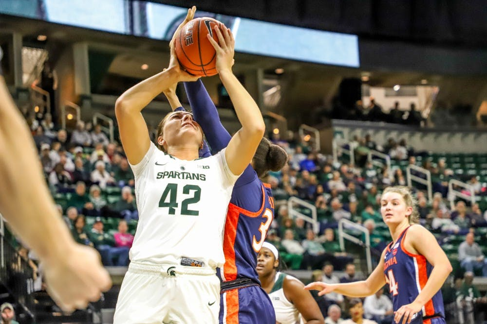 Freshman forward Kayla Belles (42) takes an elbow to the head while going up for a layup during the game against Virginia on Nov. 28, 2018 at Breslin Center. The Spartans lead the Cavaliers 46-26 at halftime.