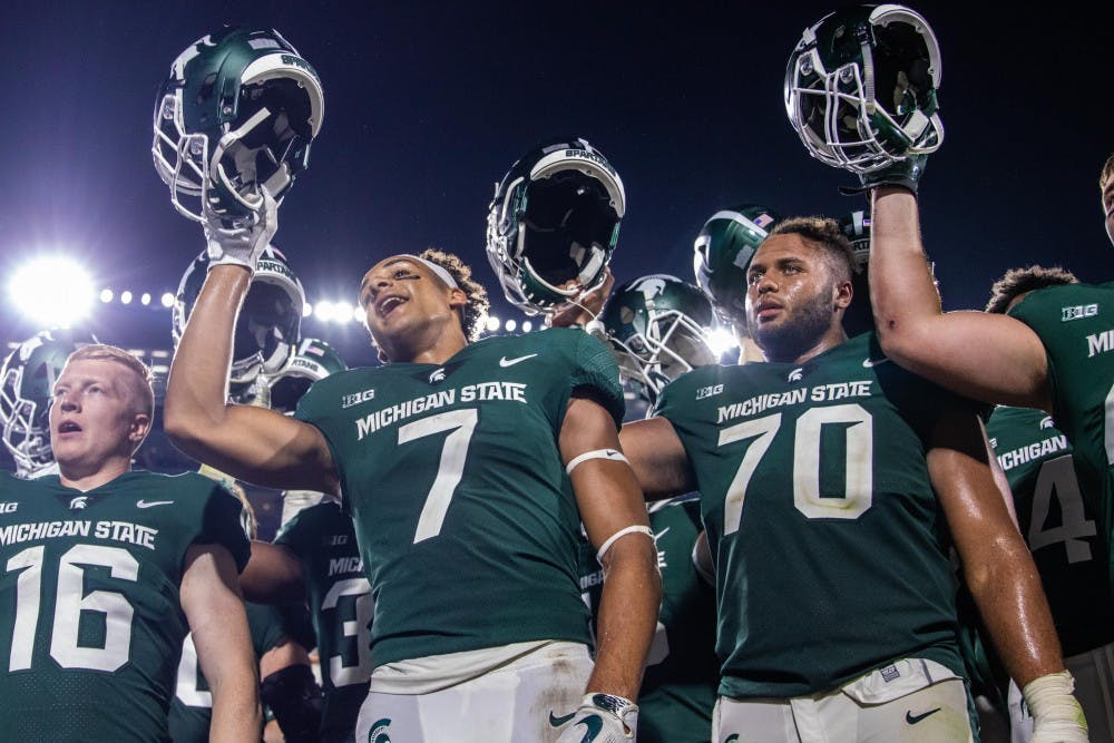 Sophomore wide receiver Cody White (7) and junior offensive lineman Tyler Higby (70) celebrate in front of the student section after the game against Utah State on Aug. 31 at Spartan Stadium. The Spartans defeated the Aggies, 38-31.