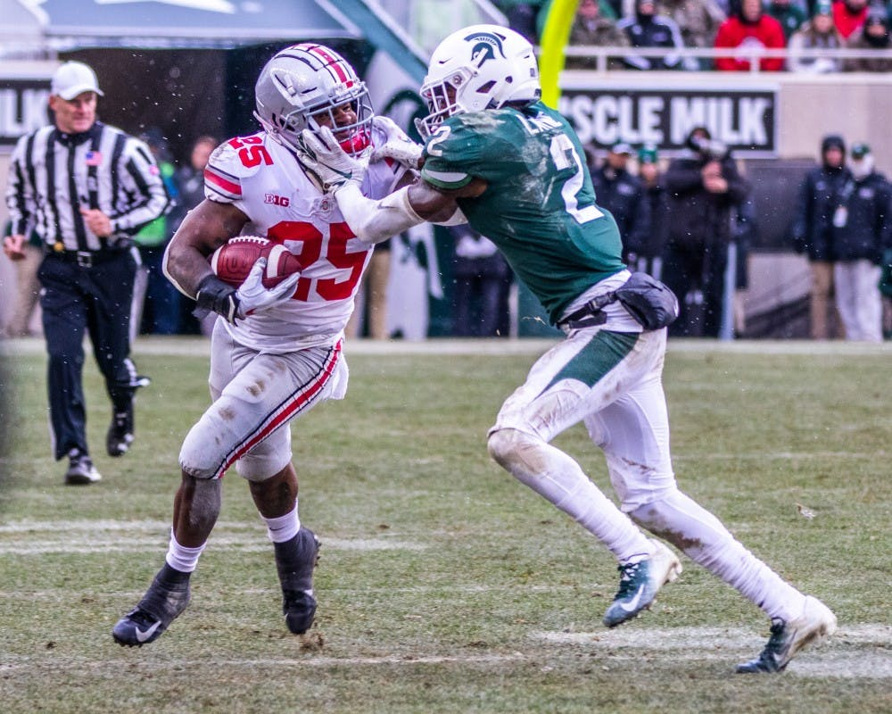Junior cornerback Justin Layne (2) attempts to tackle Ohio State running back Mike Weber Jr. (25) during the game against Ohio State Nov. 10, 2018. The Spartans fell to the Buckeyes, 26-6.