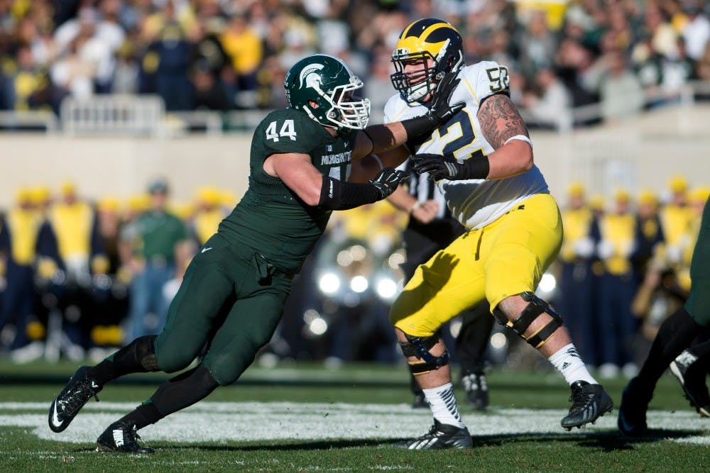 <p>Senior defensive end Marcus Rush tries to push past Michigan offensive lineman Mason Cole on Oct. 25, 2014, at Spartan Stadium. The Spartans defeated the Wolverines, 35-11. Julia Nagy/The State News</p>