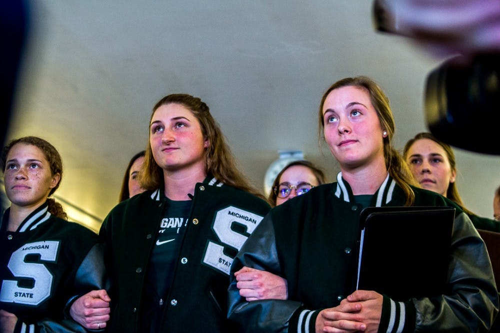 <p>From left to right, social relations and policy senior Kasidy Higgings, music education senior Nicole Marek, and kinesiology senior Lindsey Klei lock arms while addressing the media before walking to meet with the Board of Trustees on Jan 29, 2018 at Jenison Fieldhouse. The team compiled a list of their expectations in regards to how MSU handles sexual assault to present at the meeting. Larry Nassar served as the rowing team's physician from 1998-2016 and survivors of his abuse still remain on MSU women's rowing team.&nbsp;</p>