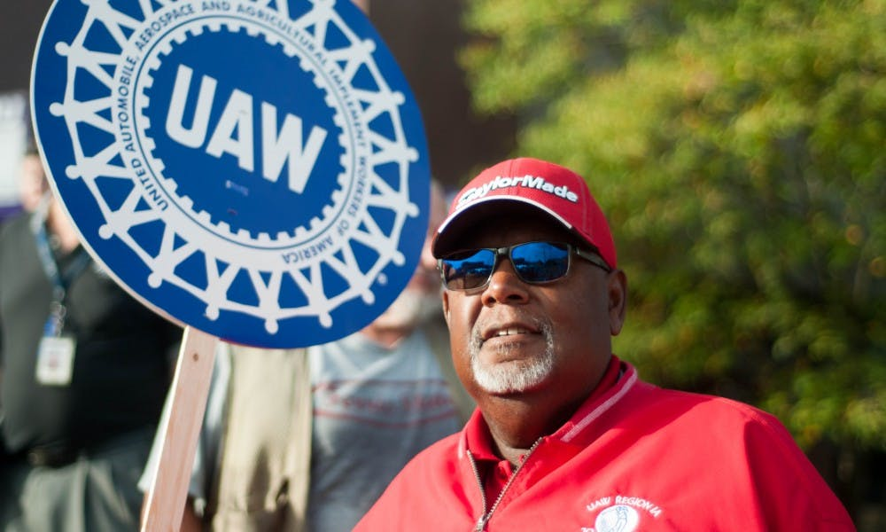 <p>UAW 6000 president Ed Mitchell holds a UAW sign during a protest of state workers' bargaining rights on Sept. 20, 2017 outside the Capitol Commons Center in Lansing. Hundreds of state employees gathered at the protest.</p>