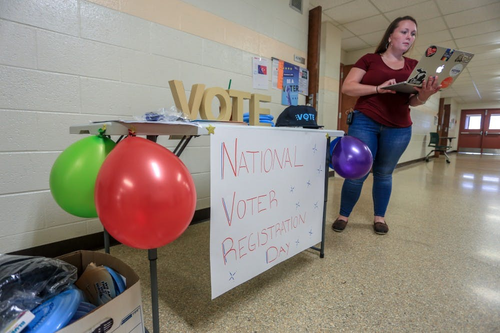 Regional Organizing Director of Next Gen America Cayley Winters helps people register to vote at Wells Hall on Sept. 25, 2018.