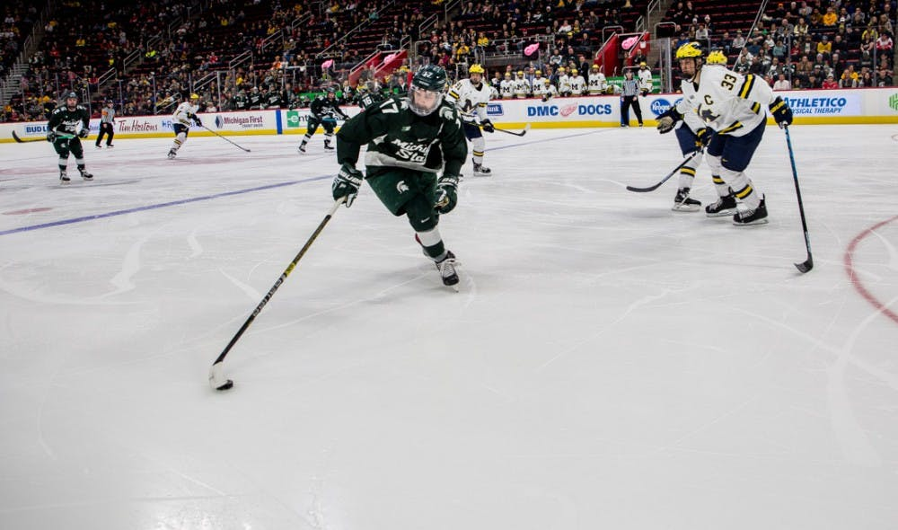 Junior left wing Taro Hirose (17) grabs the puck during the game against Michigan on Dec. 31, 2018 at Little Caesar's Arena in Detroit. The game ended in a 2-2 tie in overtime.